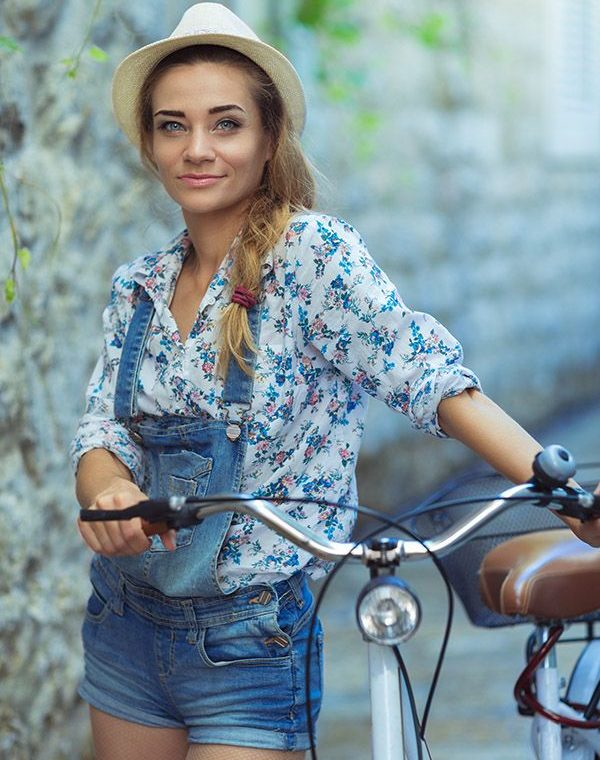 Beautiful happy woman with bicycle on street of old town